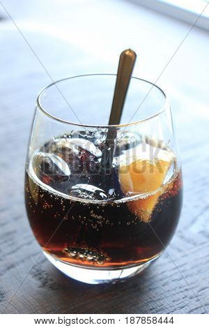 Glass of cola with ice cubes and slices of lemon