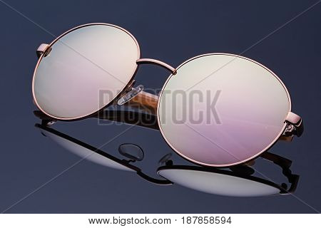 Stylish polarized reflected semitransparent almost round sunglasses with metal frame and folded ear arms. Logos removed.