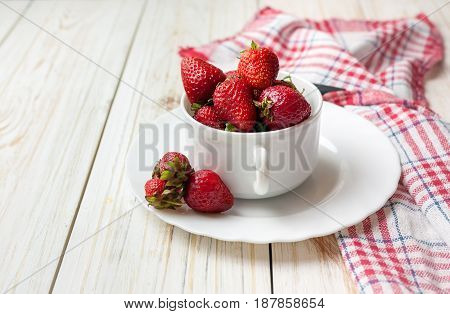 Fresh strawberry in white bowl on wooden table.