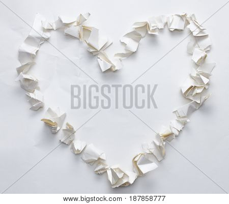 torn crumpled white paper heart shape concept