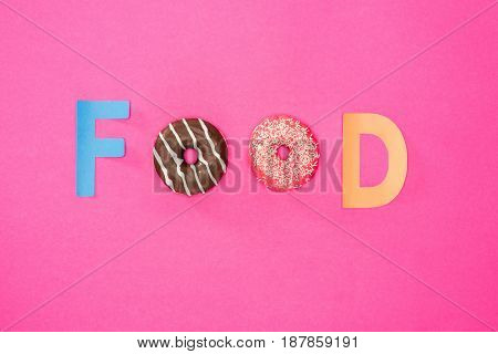 Top View Of Food Word Made From Donuts Isolated On Pink. Junk Food Background With Donuts