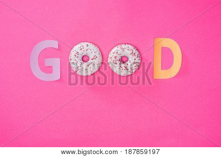 Top View Of Good Word Made From Donuts Isolated On Pink. Sweet Background With Chocolate Donuts