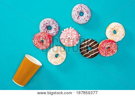 Overhead View Of Several Donuts With Various Colorful Glaze Scattered On Blue Surface