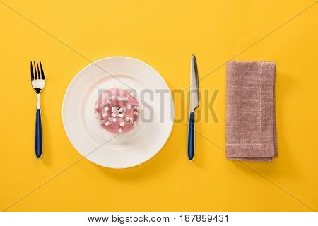 Overhead View Of Donut With Sweet Glaze In Plate And Brown Napkin Isolated On Yellow. Background In