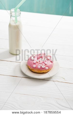 Donut With Pink Icing And Fresh Milkshake On Wooden Surface