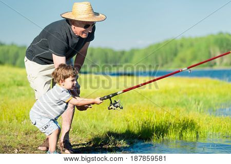 Grandson And Grandfather Fishing Together. Color Image, Toned Image