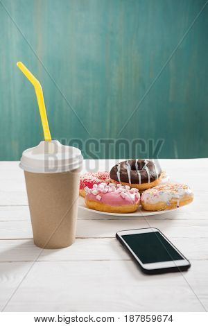 Unhealthy Breakfast With Coffee To Go, Plate Of Frosted Donuts And Smartphone Wth Black Screen On Wo