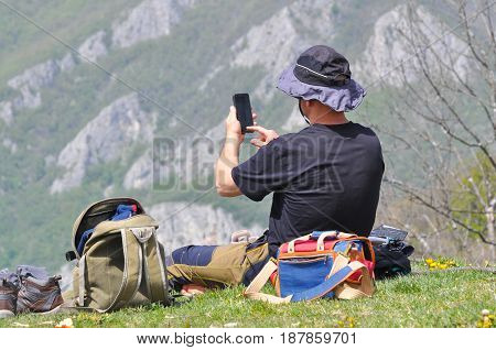 Hiker get rest on mountain peak and take photo with mobile phone. Man get rest and write on mobile on the top of hill