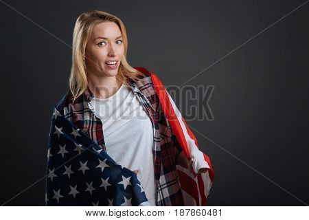 Proud of my heritage. Stunning gorgeous lively woman doing a patriotic photoshoot and posing with Stars and Stripes while standing isolated on grey background