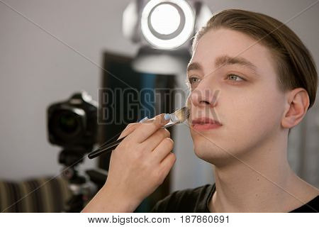 Hand of beautician putting makeup on a man. Horizontal indoors shot. Male beauty, gender equality concept.