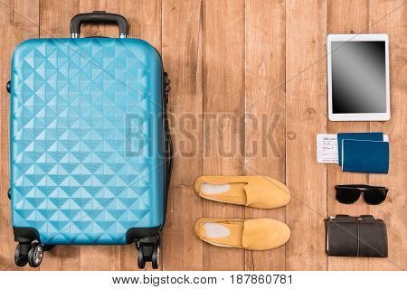 Flat lay with travel accessories on the floor. Baggage shoes passports wallet digital tablet.