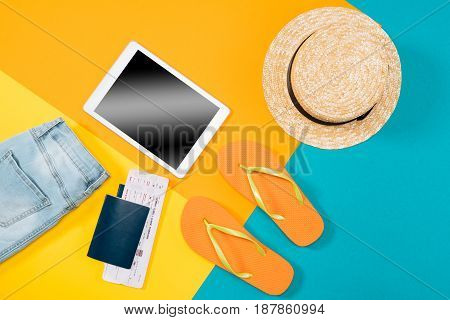 Top View Of Orange Flip Flops, Passports, Ticket, Digital Tablet And Clothes On Colored Background.