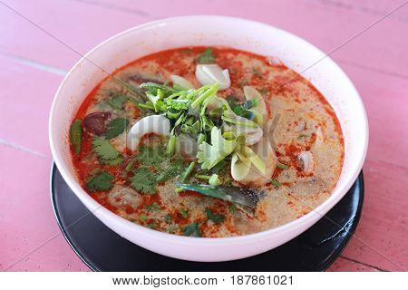 Tom Yum Goong in white bowl on pink wood of foods table background.
