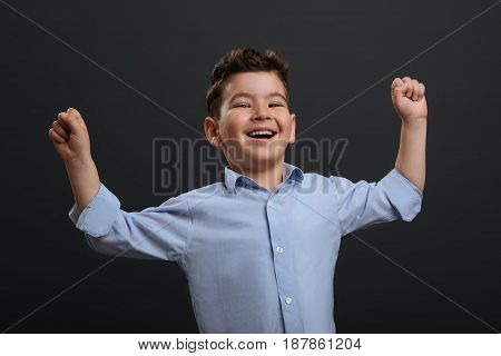 Emotional kid. Charismatic charming expressive child cheering while holding his hands up and standing isolated on grey background
