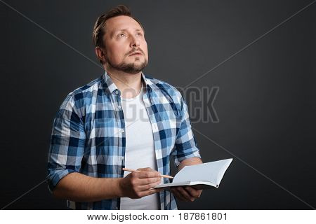 Looking for inspiration. Enchanting young thoughtful man working on a poem and using his journal for writing it down