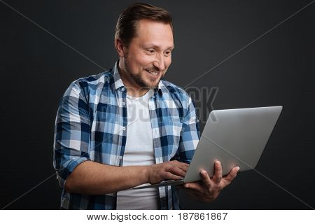 Sharing exciting news. Focused good looking nice man typing a letter while holding his computer and standing isolated on grey background