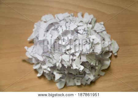 A bunch of scraps of white paper with text on a brown table