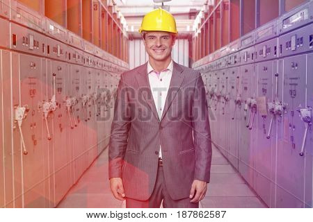 Portrait of smiling young male supervisor standing in control room