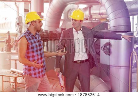 Serious manager showing something to worker in industry