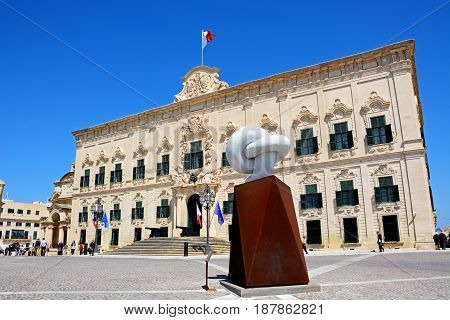 VALLETTA, MALTA - MARCH 30, 2017 - View of the Auberge de Castille in Castille Square with tourists enjoying the setting and the Bianco Carrara marble sculpture in the foreground Valletta Malta Europe, March 30, 2017.