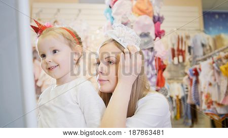 Children shopping - mom tries on a white headband next to his daughter, close up
