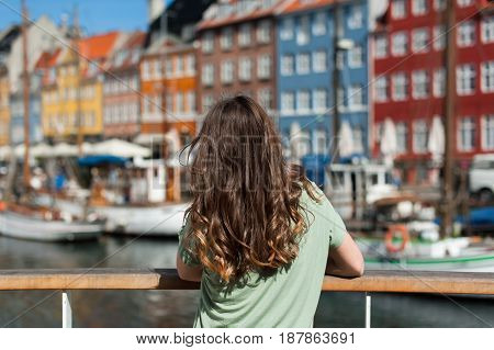 Tourist woman admiring the colored old houses, sitting at the Nyhavn harbor pier Copenhagen, Denmark. Visiting Scandinavia, famous European destination.