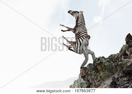 Businessman carrying zebra . Mixed media