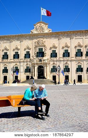 VALLETTA, MALTA - MARCH 30, 2017 - View of the Auberge de Castille in Castille Square with a couple sitting on a bench in the foreground Valletta Malta Europe, March 30, 2017.