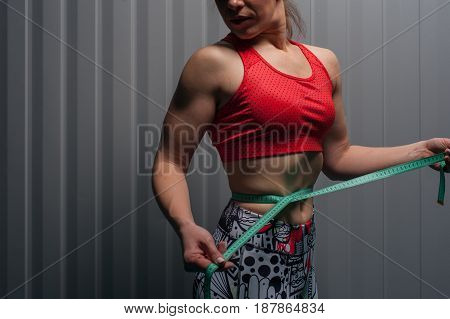 Cropped shot of female adult wearing red top with measuring tape. Fit sporty woman posing against grey wall. Fitness motivation and weight loss concept.