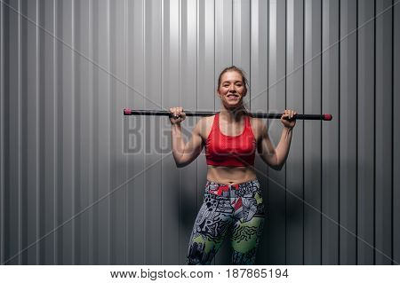 Young sporty smiling woman wearing red top with bodybar on shoulders. Sports girl posing against grey wall. Fitness, sports and healthy lifestyle.