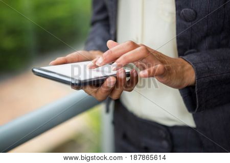 Close-up of businesswoman using mobile phone at conference centre