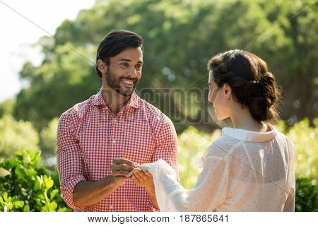 Happy man putting engagement ring on woman at park