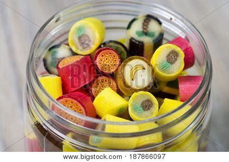 Many sweet colorful candies in opened glass jar wooden backround