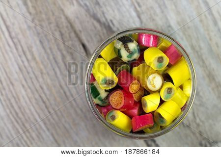 Many sweet colorful candies in opened glass jar on wooden background top view
