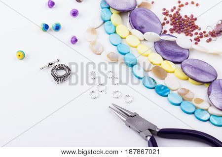 Jewelry making components. Glass and seed beads gemstone beads metal rings silver toggle pliers on white background. Selective focus.
