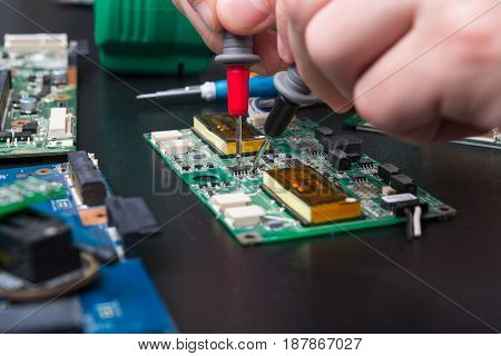 Electronic circuit board inspecting close up. Engineer measuring computer component, maintenance support and repairing service concept.