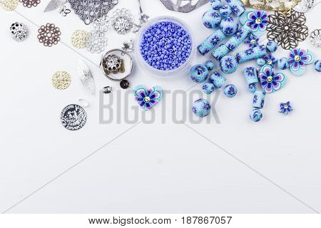 Seedbeads metal findings polyclay bead mix on white background. Hobby handmadefine arts. Selective focus. Top view.