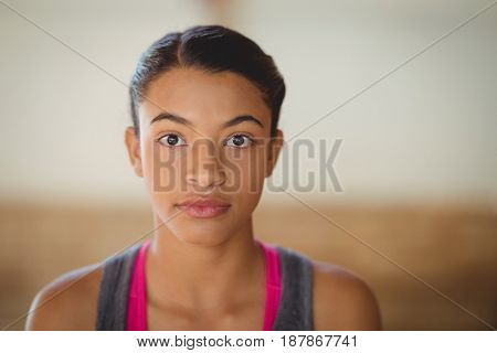 Portrait of high school girl standing in basketball court