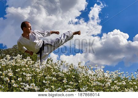 Against the backdrop of nature and sky man is beating leg