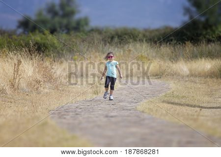 Lonely girl walking away on stone ground in countryside