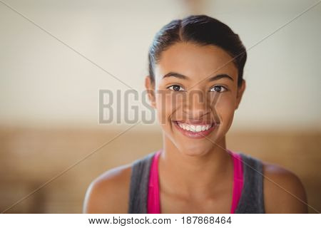 Portrait of high school girl smiling while standing in basketball court