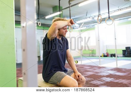 sport, fitness, lifestyle and people concept - tired man wiping sweat from his forehead sitting on jump box in gym