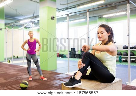 sport, training and people concept - women with fitness tracker and medicine ball in gym