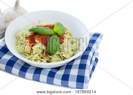 High angle view of pasta served in bowl on napkin against white background