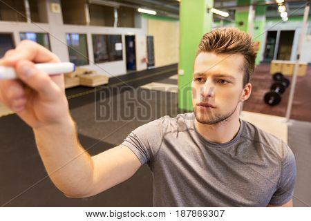 sport, fitness and people concept - man writing note to whiteboard in gym