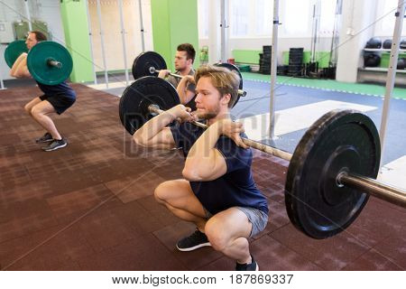 fitness, sport and people concept - men with barbells doing squats at group training in gym