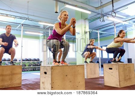 fitness, sport, training and exercising concept - group of people with heart-rate trackers doing box jumps in gym