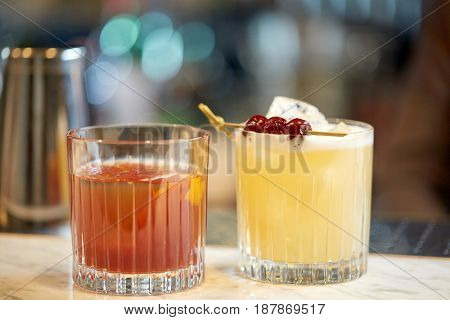 alcohol drinks and luxury concept - glasses of cocktails at bar