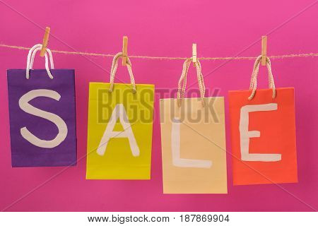 Colorful Sale Signs On Shopping Bags Hanging On Rope Isolated On Pink, Offer Sale Tags