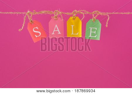 Close-up View Of Colorful Sale Sign On Tags Hanging On Rope Isolated On Pink, Offer Sale Tags